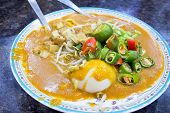 image of chinese parsley  - Malay Mee Rebus Noodle Dish Garnished with Cut Chili Peppers Tofu Chinese Celery and Hard Boiled Egg - JPG