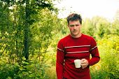 Young Man In Nature With A Mug Of Coffee