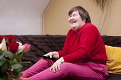 stock photo of physically handicapped  - Mentally disabled woman watching television and laughs - JPG