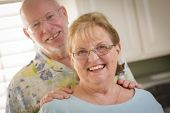 Happy Caucasian Senior Couple Portrait Inside Kitchen.