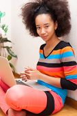 Black African American Teenage Girl With A Afro Haircut Using A Laptop Computer