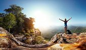 pic of wild adventure  - Hiker with backpack enjoying valley view from top of a mountain - JPG