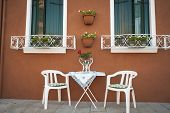 Table And Chairs Outside A House, Burano, Italy