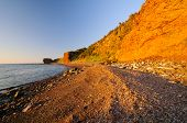 Gravel Beach In The Red Of Sunset