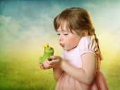 Little girl kissing a frog prince
