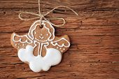 Gingerbread angel hanging over wooden background