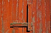 A rustic red barn door and lock