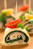 image of crepes  - Crepe rolls as finger food filled with spinach and ham garnished with cherry tomato and watercress served on wooden board  - JPG