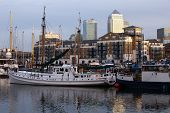 LONDON - NOV 12 2013 : Leisure boats lie docked in Limehouse Basin with Canary Wharf as a backdrop.