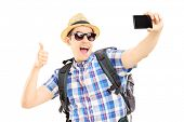 Male tourist with backpack taking pictures of himselves with mobile phone and giving thumb up isolat