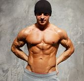 stock photo of beanie hat  - Handsome man with muscular torso in beanie hat posing - JPG