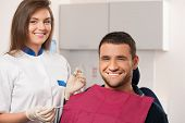Happy male patient and smiling female dentist at dental surgery