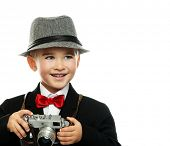 Little boy in hat and black jacket with vintage camera isolated on white background