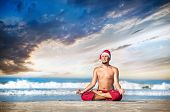 image of padmasana  - Christmas yoga meditation in padmasana lotus pose by man in red trousers and Christmas hat on the beach near the ocean in India - JPG