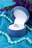 Flowers  and engagement ring on blue cloth