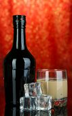 foto of bailey  - Baileys liqueur in bottle and glass on red background - JPG