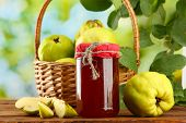jar of jam and quinces with leaves in basket, on green background