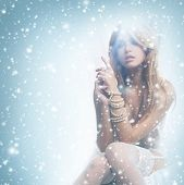 stock photo of redhead  - Young and sexy redhead woman in white lingerie over the winter background with the snow - JPG