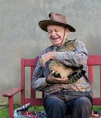pic of toothless smile  - Old man hugging his cat and laughing - JPG