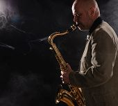 picture of saxophone player  - Adult musician playing tenor saxophone profile view smoky background - JPG