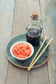 image of zingiber  - Pickled ginger with soy sauce and wooden chopsticks on plate - JPG