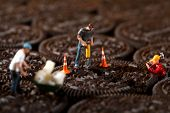 Miniature Construction Workers in Conceptual Imagery With Cookies