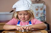 image of ginger man  - A cute young boy is baking and cutting out a gingerbread man - JPG