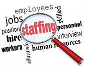 Picture of staffing words magnifying glass employees hiring positions.