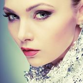 Beautiful girl with silver metallic foil on a neck, isolated on a light - grey background, emotions, cosmetics