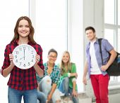 happiness and people concept - smiling young woman in casual clothes with wall clock showing 8 ocloc