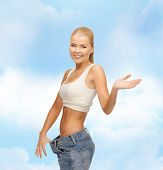 fitness, diet and healthcare concept - sporty woman showing big pants