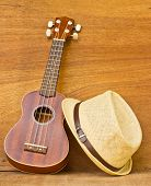 stock photo of ukulele  - The ukulele and a hat is placed on a wooden floor - JPG