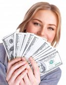 Closeup portrait of young lady holding in hands and showing a wad of american dollars, isolated on w