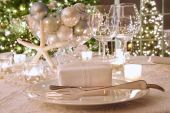 Elegantly Lit  Holiday Dinner Table With White Ribboned Gift