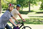Portrait of smiling woman with man riding bicycles in a park