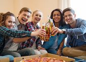 Group of young friends with pizza and bottles of drink celebrating in home interior
