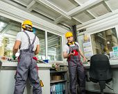 stock photo of heavy equipment operator  - Two operators wearing safety hat in a factory control room - JPG