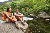 Hiking couple of hikers in outdoor activity wearing backpacks relaxing. Woman and man hiker looking