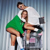 Two Beautiful Young Girls With A Skateboard, Roller Scates And A Supermarket Trolley
