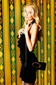 Fashion shot of a beautiful blonde model holding purse.