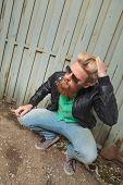 young casual bearded man crouching and passing his hand through his hair while looking away from the