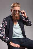casual young man with a long red beard sitting and looking into the camera while taking off his sunglasses. in a gray background studio