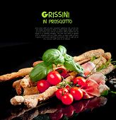 Grissini with prosciutto crudo and vegetables on black
