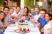 Large Group Of Young Friends Enjoying Outdoor Meal Together