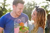 Romantic Man Giving Woman Bunch Of Flowers