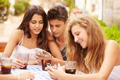 Group Of Teenage Friends Using Mobile Phone Sitting At Caf�?�¢??