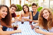 Group Of Teenage Friends Sitting Together At Caf�?�¢??