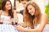 Teenage Girl Using Mobile Phone Sitting At Caf�?�¢?? With Friends
