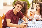 Teenage Boy Using Mobile Phone Sitting At Caf�?�¢?? With Friends