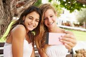 Two Teenage Girls Sitting On Bench Taking Selfie In Park